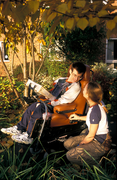Disabled male with carer in the garden of residential home,