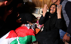 April 13, 2018 - Khan Yunis, Gaza Strip - Palestinians mourn over the body of Abdullah al-Shahari, 28, who was killed by Israeli security forces during clashes at the Israel-Gaza border the previous day, during his funeral in Khan Yunis, in southern Gaza Strip. (Credit Image: © Ashraf Amra/APA Images via ZUMA Wire)