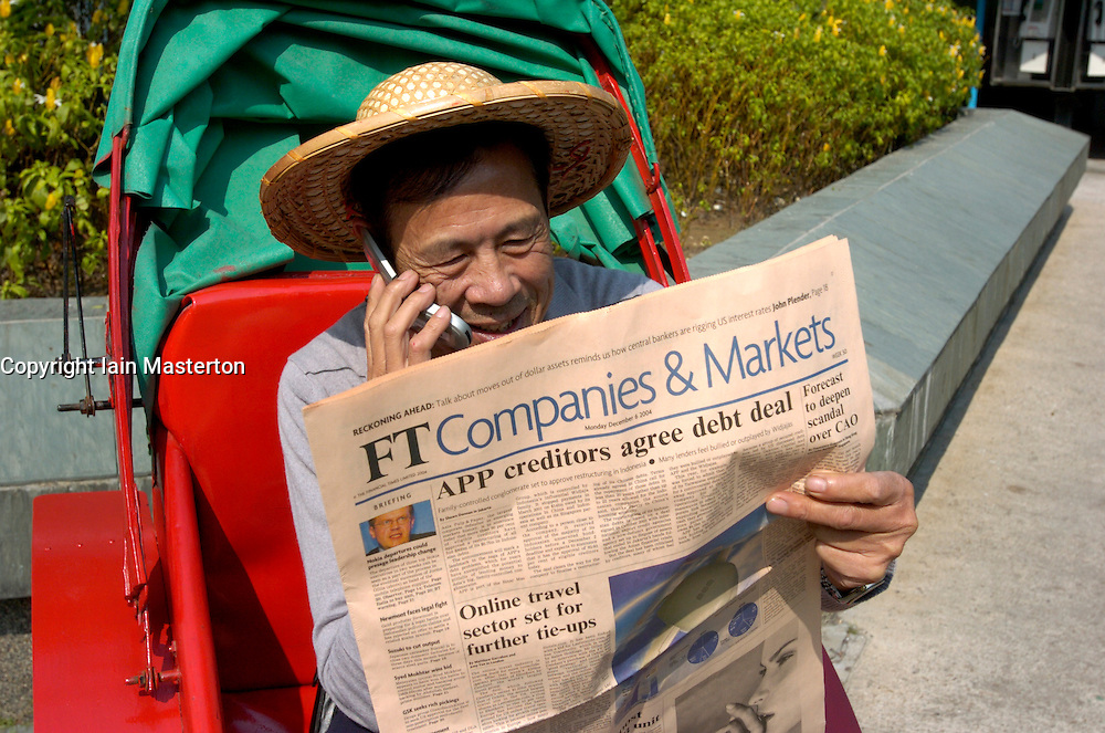 Chinese man in rickshaw reading Financial Times newspaper and calling stockbroker on telephone  in Hong Kong China
