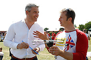 Photo by Andrew Tobin/Tobinators Ltd - 07710 761829 - Steve Barclay MP (Conservative N.E. Cambridgeshire) (L) gets some lessons from current world champion Rob Bresler (R) during the World Peashooting Championships held at Witcham, Cambridgeshire, UK on 13th July 2013. Run in conjunction with the village fair, the Championships have been held in Witcham since 1971 when they were started by a Mr Tyson, the village schoolmaster, in order to raise funds for the village hall.Competitors come from as far afield as the USA and New Zealand to attempt to win the event. The latest technology is often used, including laser sights and titanium and carbon fibre peashooters. All peashooters must conform to strict length rules, not exceeding 12 inches, and have to hit a target 12 feet away. Shooting 5 peas at a plasticine target attached to a hay bale, the highest scorers move through the initial rounds to a knockout competition, followed by a sudden death 10-pea shootout.