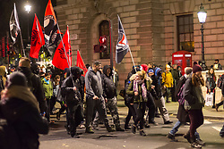 London, November 05 2017. Anti-capitalists gather in Trafalgar Square, London for the annual 'Million Mask March' which happens on November 5th every year, with many of the protesters donning 'V' For Vendetta Guy Fawkes masks. Past marches have turned violent with police horses shot by fireworks and police vehicles burned. PICTURED: Protesters with anarchist flags march along Whitehall. © Paul Davey