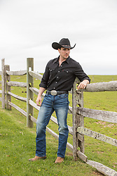 hot cowboy leaning on a rustic fence