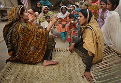 Mukhtar Mai, 33, right, and her best friend Naseem Akhter, talk with relatives during a visit her to aunts house, Meerwala, Pakistan, April 28, 2005. Mai, went against the Pakistani tradition of committing suicide when she brought charges against the men who gang raped her nearly three years ago. With money from the ruling she opened two schools, one for girls, the other for boys, citing that education is the only thing that will stop such acts from happening.
