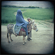 A boy travels with his mother on a donkey in Badakshan.