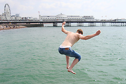 © Licensed to London News Pictures. 26/07/2014. Brighton, UK. Kids jump of the jetty in the sea on Brighton beach. The weather is expected to reach temperatures around the 26C in Brighton and the South Coast. Photo credit : Hugo Michiels/LNP