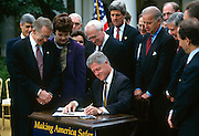 U.S. President Bill Clinton signs into law the Crime bill during a ceremony on the South Lawn of the White House October 3, 1996 in Washington, DC.  Senators Harry Reid, Dianne Feinstein, John Kerry and Joe Biden look on.