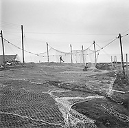 Geordie Pullar working to repair salmon nets drying at Fishtown of Usan, Angus.<br /> Ref. Catching the Tide 01/02/11 (11th April 2002)<br /> <br /> The once-thriving Scottish salmon netting industry fell into decline in the 1970s and 1980s when the numbers of fish caught reduced due to environmental and economic reasons. In 2016, a three-year ban was imposed by the Scottish Government on the advice of scientists to try to boost dwindling stocks which anglers and conservationists blamed on netsmen.