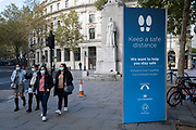 In front of the statue to WW1 heroine Edith Cavell, young women walk past a City of Westminster board urging the public to socially distance in the West End during the second (Autumn) wave of the Coronavirus pandemic, on 8th October, 2020, in London, England. (Richard Baker / In Pictures via Getty Images)