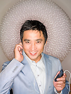 Headshot of asian man (40-45 years old) smiling while listening to mp3 player with earbuds