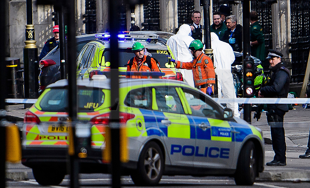 © Licensed to London News Pictures. 22/03/2017. London, UK. Police forensics examine a damaged car (grey, pictured rear) involved in the incident, at the scene of suspected terrorist attack near Houses of Parliament in Westminster, London. Photo credit: Ben Cawthra/LNP