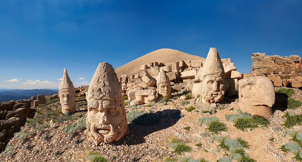 Statue head, from left, Antiochus, Commenge , Zeus, Apollo, Herekles & Eagle, in front of the 62 BC Royal Tomb of King Antiochus I Theos of Commagene, west Terrace, Mount Nemrut or Nemrud Dagi summit, near Adıyaman, Turkey .<br /> <br /> If you prefer to buy from our ALAMY PHOTO LIBRARY  Collection visit : https://www.alamy.com/portfolio/paul-williams-funkystock/nemrutdagiancientstatues-turkey.html<br /> <br /> Visit our CLASSICAL WORLD HISTORIC SITES PHOTO COLLECTIONS for more photos to download or buy as wall art prints https://funkystock.photoshelter.com/gallery-collection/Classical-Era-Historic-Sites-Archaeological-Sites-Pictures-Images/C0000g4bSGiDL9rw
