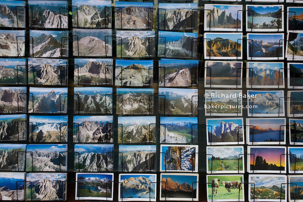 Detail of postcard souvenirs of Dolomite mountain scenes in a shop selling tourist memorablia on Passo Falzarega (Pass) in south Tyrol, Italy.