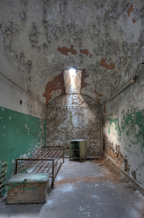 """Abandoned cell at Eastern State Penitentiary, Philadelphia, PA (US). HDR image. Opened in 1829, and dubbed the """"Pennsylvania System"""" or Separate system, originated and encouraged solitary confinement as a form of rehabilitation. The prison was closed and abandoned in 1971, now operates as a museum and historic site."""