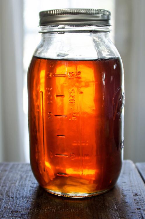 A glass mason jar full of organic Maine maple syrup, Bar Harbor, Maine.