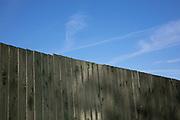 Garden fence against a blue sky in Birmingham, United Kingdom.