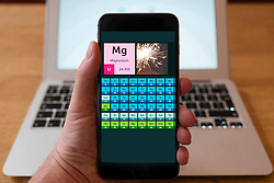 Using iPhone smartphone to display periodical table of the elements educational science application