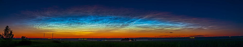 A superb showing of noctilucent clouds (NLCs) on June 27, 2021, with the colours very prominent, even to the eye. The colours transition from the red and oranges of the solstice twilight, through to yellows and even greens above (these were obvious to the eye), then to the cyan and electric blue of the clouds themselves. The tops of the clouds fade to a deep red as they are being illuminated there by the setting Sun at their altitude and latitude and so appear red, with that red edge decreasing in altitude as the evening progressed as the Sun set lower below the horizon.<br /> <br /> A widespread area of very clear sky locally and far to the north may have contributed to the better visibility of the colours as the light from the Sun had a clearer path through the atmosphere. <br /> <br /> This was June 27-28, 2021, in a particularly widespread display that started the evening with the clouds filling the northern half of the sky,. This was from home and is a panorama stitched from 9 segments, each with the 24-105mm f/4 RF lens at 67mm, and Canon R6 camera.
