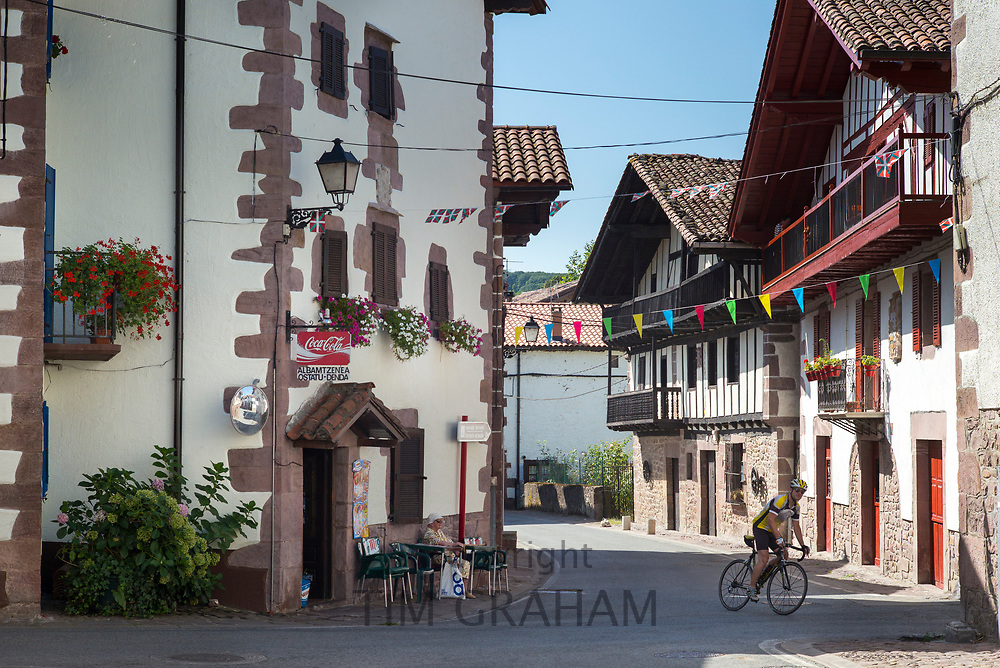 Cyclist passing typical Basque houses in town of Erratzu in Valle de Baztan, Basque Country, Spain
