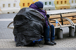 File photo dated 08/09/15 of a homeless person resting on a bench as Theresa May has announced a £40 million package designed to prevent homelessness by intervening to help individuals and families before they end up on the streets.