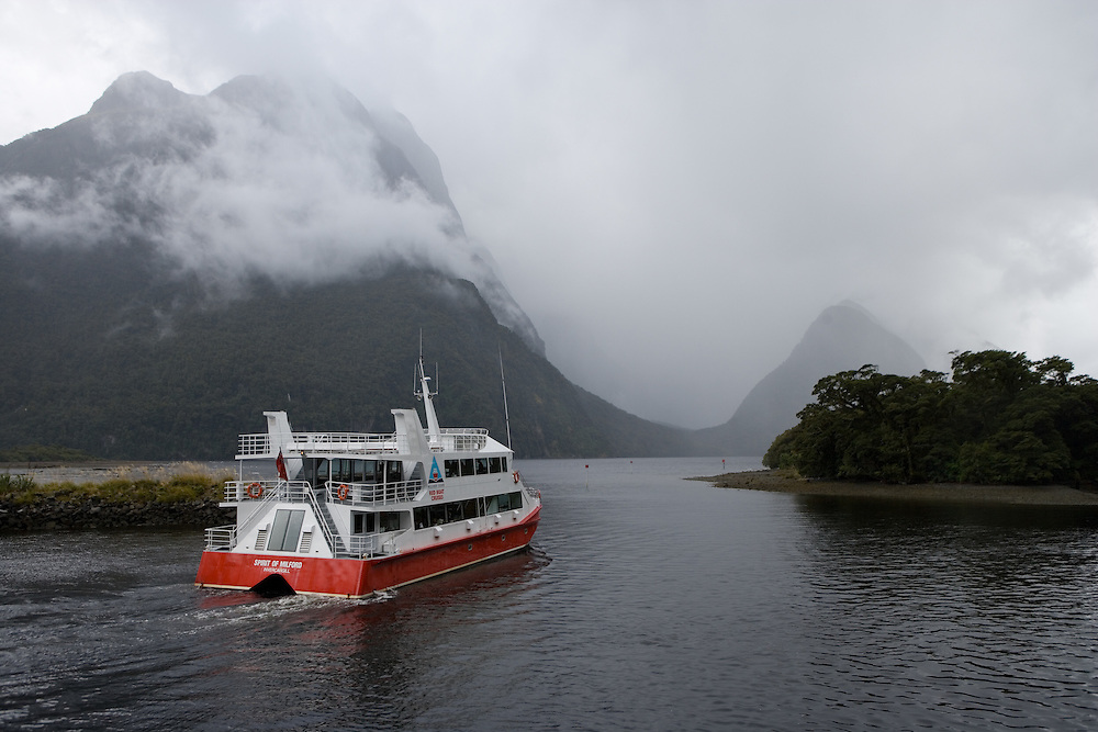 Cruise boat leave the wharf  to take tourists on a two hour cruise through Milford Sound in Fiordland National Park in New Zealand.
