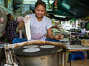 "03 APRIL 2014 - BANGKOK, THAILAND:  A woman makes ""roti"" a type of unleavened Indian flat bread in Khlong Toey Market. Roti is popular throughout Thailand and is used as starch for southern Thai curries (instead of rice) and a snack, filled with fruits (especially bananas) or sugar.  Khlong Toey (also called Khlong Toei) Market is one of the largest ""wet markets"" in Thailand. The market is located in the midst of one of Bangkok's largest slum areas and close to the city's original deep water port. Thousands of people live in the neighboring slum area. Thousands more shop in the sprawling market for fresh fruits and vegetables as well meat, fish and poultry.     PHOTO BY JACK KURTZ"