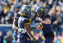 Nov 10, 2018; Morgantown, WV, USA; West Virginia Mountaineers running back Kennedy McKoy (6) runs for a touchdown and celebrates with teammates during the second quarter against the TCU Horned Frogs at Mountaineer Field at Milan Puskar Stadium. Mandatory Credit: Ben Queen-USA TODAY Sports