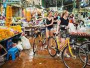 "11 AUGUST 2016 - BANGKOK, THAILAND:       Tourists on a group tour push their bicycles through Pak Khlong Talat in Bangkok. Pak Khlong Talat (literally ""the market at the mouth of the canal"") is the best known flower market in Thailand. It is the largest flower market in Bangkok. Most of the shop owners in the market sell wholesale to florist shops in Bangkok or to vendors who sell flower garlands, lotus buds and other floral supplies at the entrances to temples throughout Bangkok. There is also a fruit and produce market which specializes in fresh vegetables and fruit on the site. It is one of Bangkok's busiest markets and has become a popular tourist attraction.  PHOTO BY JACK KURTZ"