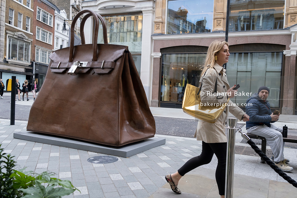 A workman admires a blonde woman as she walks past the oversized artwork of a hand bag accessory entitled 'Bag of Aspirations' (2019) by the Greek artist Kalliopi Lemos (b1951) located on New Bond Street, on 30th October 2020, in London, England.