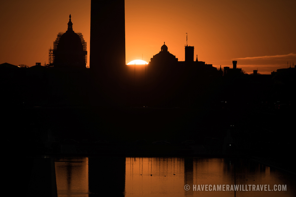 WASHINGTON, DC--At left is the US Capitol Dome, with the base of the Washington Monument in the center of frame. During the spring and fall equinox the sun rises directly to the east and lines up along the National Mall.