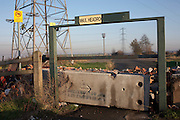 Avoiding fly-tippers, a barricaded and disused car park entrance is near electricity pylons at Dartford, Kent.