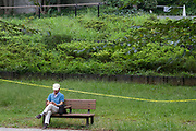 A man sits on a  park bench using a smartphone  in Shibakoen (Shiba Park) with yellow tape restricting access to the park land around him in an effort to combat the spread of the Coronavirus. Minato Ward, Tokyo, Japan. Sunday September 12th 2021.