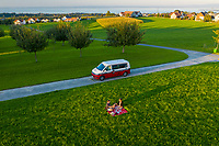 Morschwil, Switzerland - 9 September 2020: Aerial view of two people having a picnic on the grass next to their motorhome. Morschwil, Switzerland.