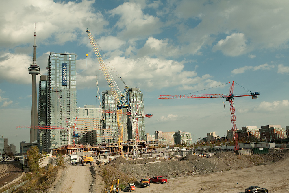 Numbers of construction cranes rasing new residential condominiums in Toronto's Library District, seen from the west with the CN Tower in the background.