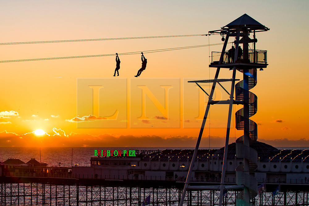 © Licensed to London News Pictures. 28/12/2017. Brighton, UK. Members of the public take a ride on the zip wire attraction in Brighton and Hove as the sky turns golden at sunset. Photo credit: Hugo Michiels/LNP