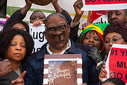"Lodon, February 21st 2015. Dozens of exiled Zimbabweans gather outside their embassy in London proclaiming Mugabe's last birthday in office. Singing and dancing as they have done every Saturday since 2002, the group spoke with passersby and added yet more names to their petition. PICTURED: ""Mugabe"" displays his birthday cake as back in Zimbabwe hundreds of guests prepare to dine on two elephants that have allegedly been butchered for his birthday celebrations at Victoria Falls."