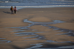 © Licensed to London News Pictures. 12/12/2020. St Ives, UK. Walkers on Porthmeor Beach in St Ives, Cornwall, at sunrise. Photo credit : Tom Nicholson/LNP