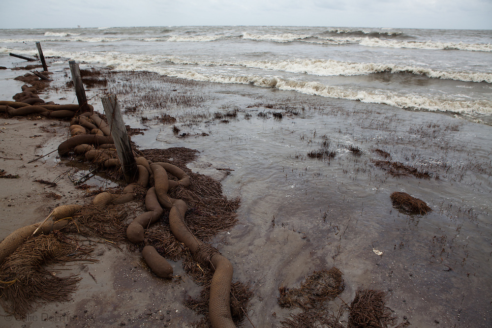 BP oil filled absorbent  boom clean up crew workers leave behind that has been washed on shore of Grand Terre Island as Louisiana's coast feels the effects of  Hurricane Alex .
