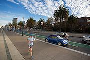 Een vrouw is aan het hardlopen langs de boulevard in San Francisco. Haar blauwe outfit komt overeen met een blauwe Volkswagen Kever die geparkeerd staat. De Amerikaanse stad San Francisco aan de westkust is een van de grootste steden in Amerika en kenmerkt zich door de steile heuvels in de stad.<br /> <br /> A woman runs at the boulevard in San Francisco. Her blue outfit matches the color of the Volkswagen Beetle parked. The US city of San Francisco on the west coast is one of the largest cities in America and is characterized by the steep hills in the city.