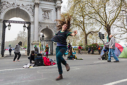 A young woman dances in front of Marble Arch as hundreds of environmental protesters from Extinction Rebellion occupy Marble Arch, camping in the square and even on the streets, blocking access to traffic on Park Lane and Oxford Street in London's usually traffic-heavy west end. . London, April 16 2019.