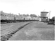 String of drop-bottom gondolas at water tank in Durango yard as viewed from the north.<br /> D&RGW  Durango, CO
