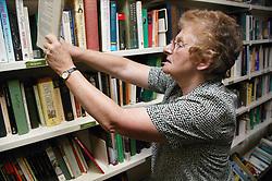 Woman volunteer working in charity shop,