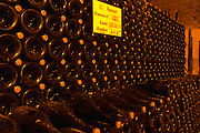 In the underground winecellar that is an old chalk quarry: thousands (4047) of bottles aging under a vault, Champagne Ruinart, Reims, Champagne, Marne, Ardennes, France, low light grainy grain