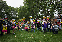 London, UK. 15th July, 2021. Anti-racist campaigners take a knee in solidarity with England footballers Marcus Rashford, Jadon Sancho and Bukaya Saka during an event on Ducketts Common organised by Haringey Stand Up To Racism. The three England footballers were subjected to racial abuse following England's Euro 2020 final defeat against Italy.