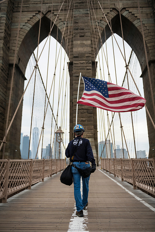 New York City, USA - March 20, 2020: Henry Lallave carries an American flag across the Brooklyn Bridge. He was walking with the flag, he said, to encourage people who were feeling fear during the coronavirus pandemic.