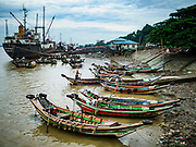22 NOVEMBER 2017 - YANGON, MYANMAR: One of the small domestic ports on the Twante Canal. The small boats are river taxis that take customers across the canal or up and down the river. Commercial freighters tie up at the jetties along the canal to off load cargo for the Yangon or take on cargo to be sent into the interior of Myanmar.    PHOTO BY JACK KURTZ