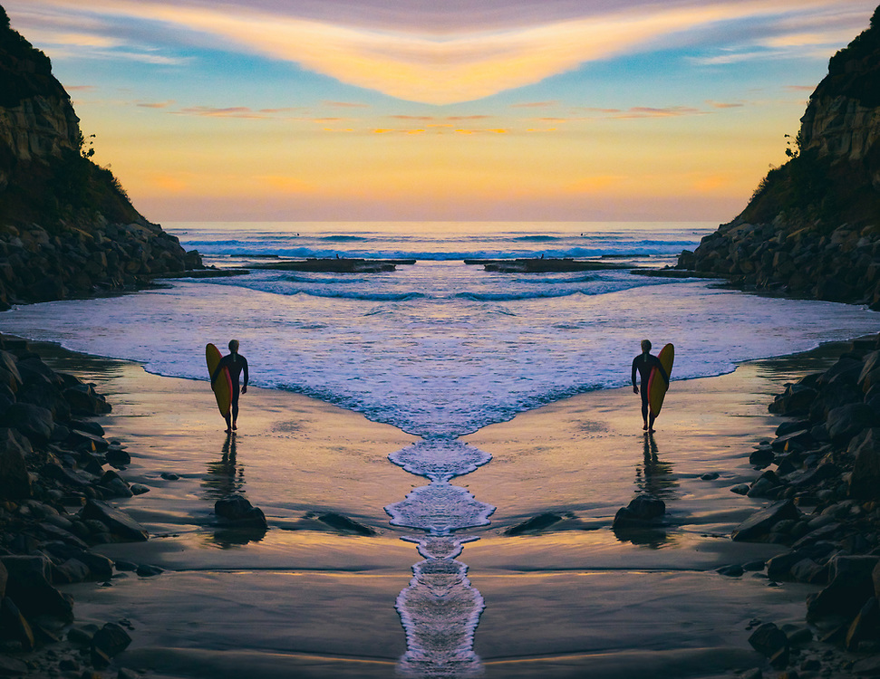 Surfer walking out at Swamis Beach at Sunset, in Encinitas, San Diego, California.