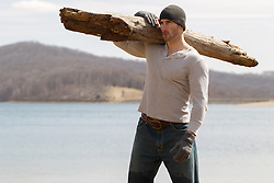 sexy man holding a large log by a lake