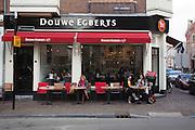 Mensen genieten op het terras van de Douwe Egberts winkel van het mooie weer.<br /> <br /> People are drinking coffee at a Douwe Egberts store in Utrecht.