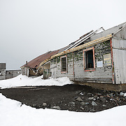 Wooden building ruins at the abandoned whaling station at Whalers Bay, Deception Island. Because of the cold temperatures, wood takes much longer to decompose than it does in warmer climates. Deception Island, in the South Shetland Islands, is a caldera of a volcano and is comprised of volcanic rock.