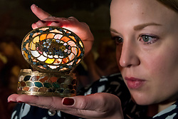 """© Licensed to London News Pictures. 07/12/2020. LONDON, UK. A staff member poses with """"A very rare gold and pietra dura 'Steinkabinett', complete with secret compartment and explanatory booklet"""" by Christian Gottlieb Stiehl"""", circa 1770, (Est. £700-£1m). Preview of Sotheby's upcoming Christmas Sale Series of Old Masters and Treasures - paintings and objects spanning 800 Years.  The sales will be at Sotheby's New Bond Street gallery.  Photo credit: Stephen Chung/LNP"""